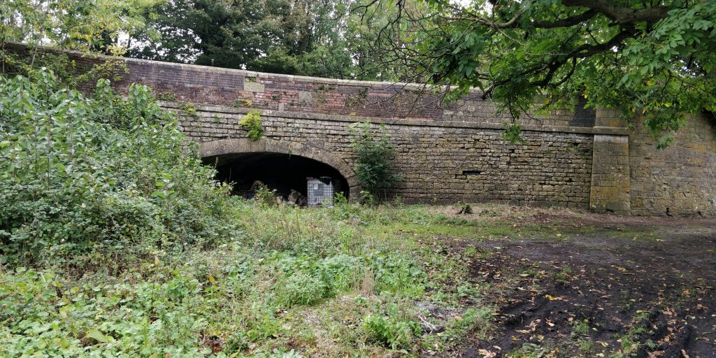 The West side of the bridge that once carried the A367 and now carries the layby. This approximately half hal way along the Somersetshire Coal Canal.
